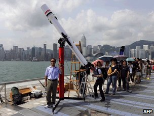 A man poses for a photograph as people queue up along the Hong Kong harbour waterfront to look through a telescope