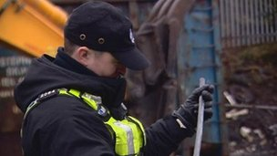 Police officer in scrap yard