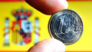 Euro coin held in front of Spanish flag