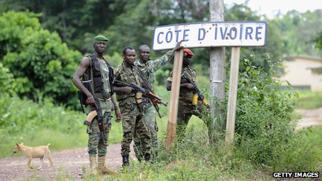 A photograph from April 2011 showing Ivorian militiamen standing on the border between Ivory Coast and Liberia
