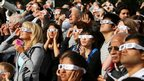 Hundreds of people gather wearing special viewing glasses gather to watch the transit of Venus at the University of Western Ontario in London, Ontario
