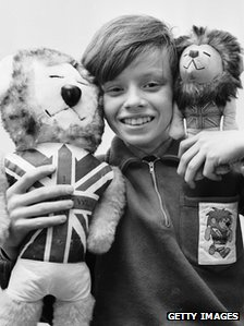 February 1966: Leo Hoye, the son of commercial artist Reg Hoye, the man who designed the world cup mascot  Willie the Lion, holding mascot toys.
