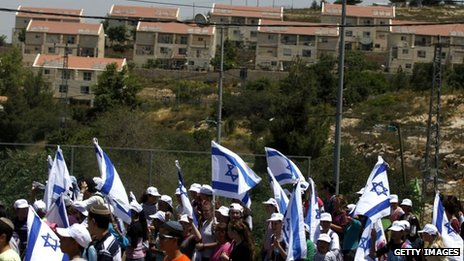 Jewish settlers wave Israeli flags during a protest near Ulpana against the decision to evacuate the illegal West Bank settlement outpost (6 June 2012)