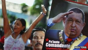A supporter of Venezuelan President Hugo Chavez holds a poster of Chavez during an United Socialist Party campaign rally in Caracas, 1 June  2012