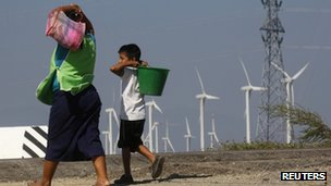 A woman and a boy walk past wind turbines and an electricity tower in La Ventosa, Mexico