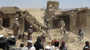 Afghan villagers gather at a house destroyed in an apparent NATO raid in Logar province, south of Kabul, Afghanistan