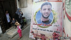 Members of Mahmoud al-Sarsak's family walk past a poster demanding his release (5 June 2012)