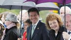 Seb Coe, chairman of the London 2012 organising committee, shelters under an umbrella as dignitaries watch the torch cross the border.