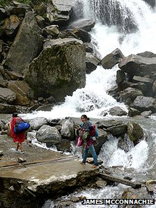 Two people walk alongside a waterfall