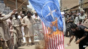Pakistani protesters burn representations of US and NATO flags during a demonstration to condemn U.S. drone strikes in the tribal areas, in Multan, Pakistan