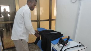 An employee of the Somalia Premium Laundry checks a rail of clothes.