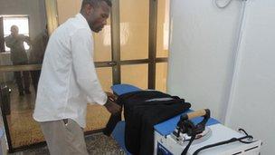 An employee of the Somalia Premium Laundry checks a rail of clothes.