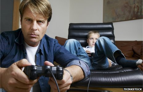 Father playing son&#039;s computer game 