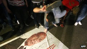 A protester hits a picture of Ahmed Shafiq with his shoe after the election results were declared