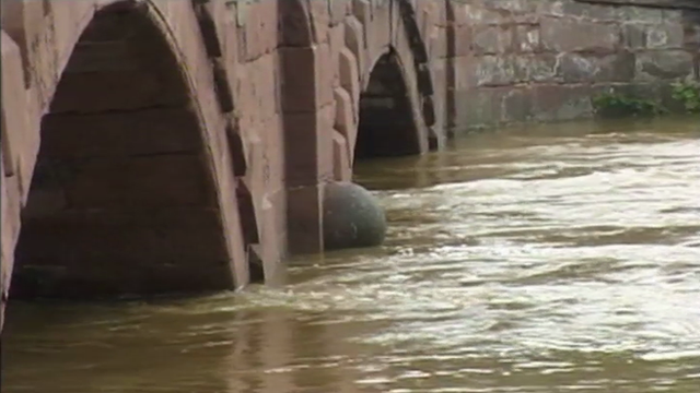 Swollen river runs under bridge
