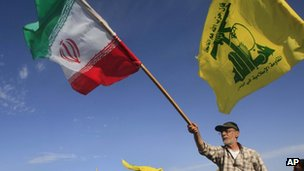 A man waves an Iranian flag at a Hezbollah rally in southern Lebanon on 25 May 2012