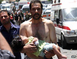 A man carries an injured child after a blast in  Qudssaya, Damascus, 8 June