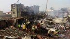 Rescue workers search for bodies of victims of a plane crash at Iju-Ishaga neighbourhood, Lagos