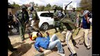 Police officers beat opposition demonstrators during a protest in Lusaka