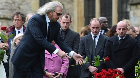 "Barry Gibb releases a rose onto his brother""s grave"