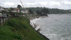A clipper yacht which drifted onto rocks at St Mawes in Cornwall