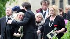 Robin Gibb's widow Dwina hugs her son RJ at the funeral of her husband.