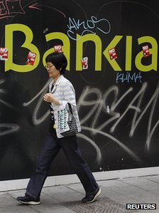 Woman walks past defaced Bankia sign in Madrid