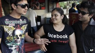 An Indian girl wears a t-shirt displaying a Facebook logo as she interacts with friends in Ahmadabad