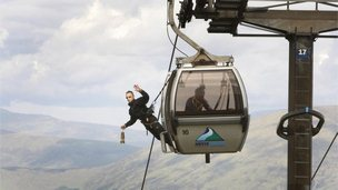Davie Austin, an employee  of the Nevis Range, carries the Olympic Flame on a gondola