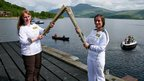 Ruth Leith (R) passes the Olympic flame to Sheila Mcneill