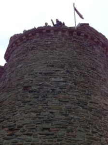 Crowds watch the torch relay from the top of Bishop&#039;s Tower