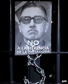 Poster of Pinochet on a barred door during protest