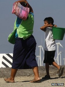 A woman and a boy walk past wind turbines and an electricity tower in La Ventosa 7 February 2012. 