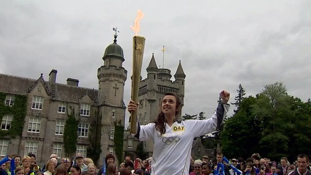 Lauren Fraser lifts the Olympic torch in front of Balmoral Castle
