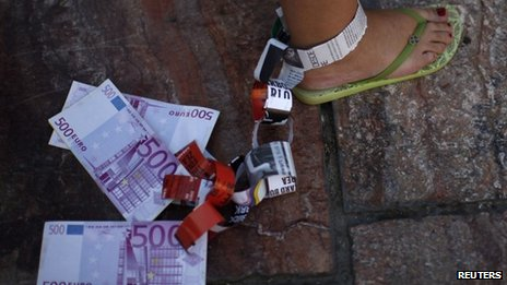 A demonstrator hangs fake Euro notes on her leg during a protest against Spain's bailout in Malaga June 10 2012.