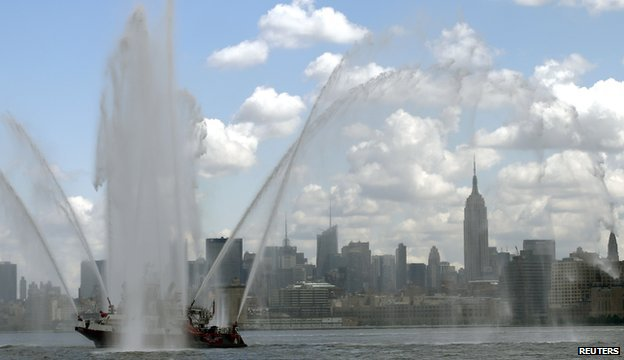 The New York City skyline and the Empire State Building are visible under the spray from a fire boat