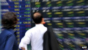 Investors looking at market board on Tokyo