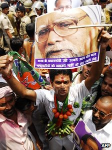 A supporter of India's opposition National Democratic Alliance holds a poster of Indian Prime Minister Manmohan Singh holds a poster during a rally in Patna on May 31, 2012,
