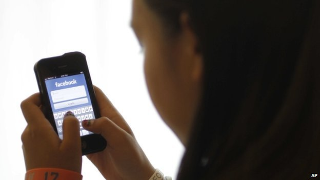 Girl using Facebook on her mobile phone