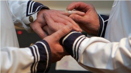 Man putting ring on finger of other man in civil partnership