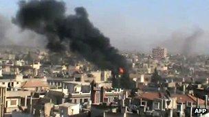 An image grab taken from a video uploaded on YouTube on 11 June 2012 shows smoke billowing from Homs which activists said was being attacked by regime forces