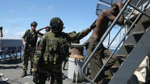 French soldiers escort suspected Somali pirates on board a warship in 2009 as part of an EU operation