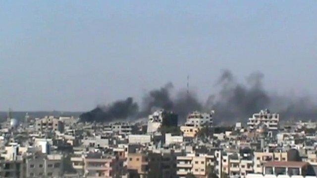 Smoke rises above buildings