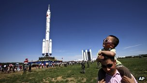 A Chinese father and son near the Long March-2F rocket carrying the Shenzhou-9 spacecraft
