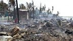 A Buddhist monk walks through a burned houses in Sittwe, northwest Burma