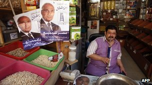 Shopkeeper with Ahmed Shafik posters in Cairo, file pic