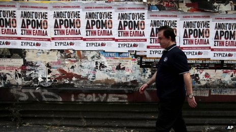 A man walks past election campaign posters in Greece's capital Athens