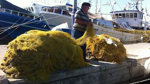 Fisherman Yiannis gathers his net in Greece's port town of Chalkida.