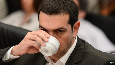 Alexis Tsipras takes a drink during a news conference in Athens, 12 June