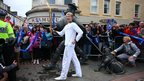 Mark Szaranek carries the Olympic flame next to the Desperate Dan statue in Dundee